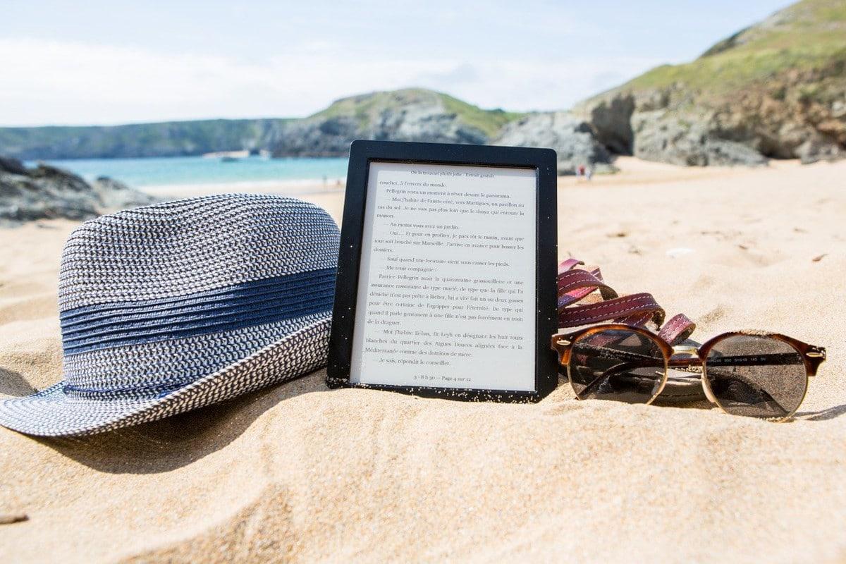 ereader en la playa junto a un sombreo y unas gafas de sol